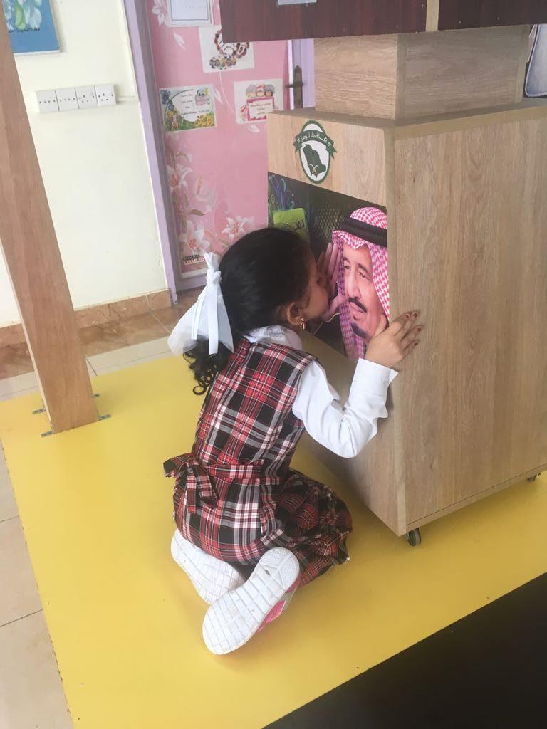 طفلة يتيمة تقبل صورة الملك سلمان.. في مشهد مؤثر