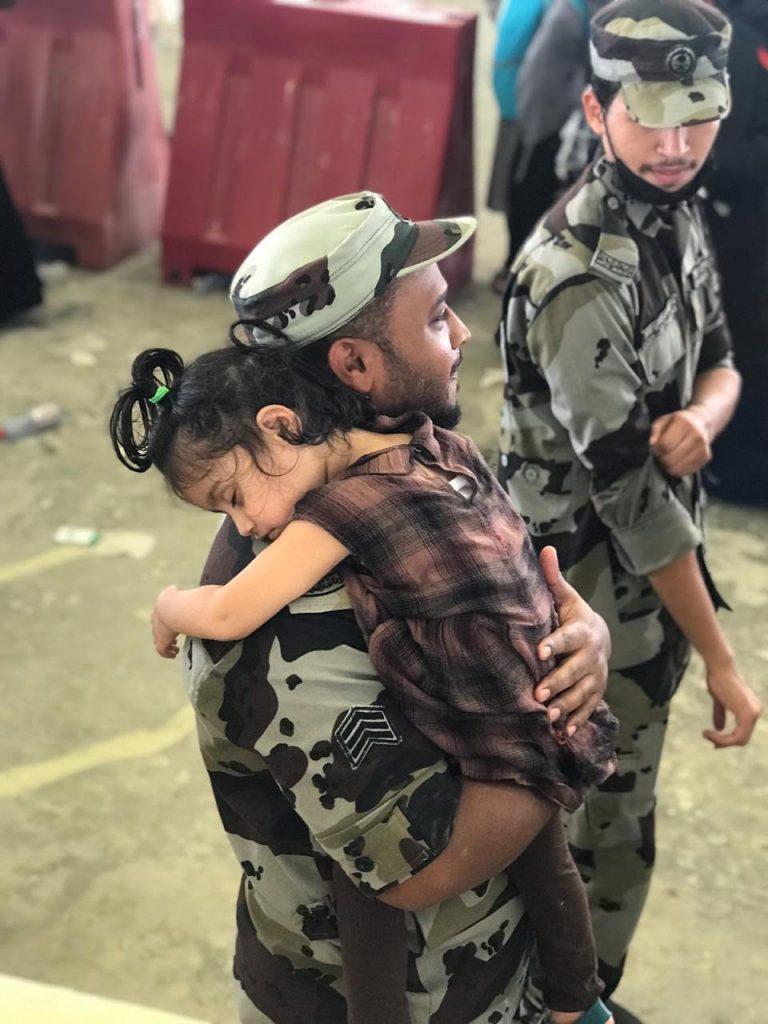 رجل أمن يحمل طفلة خلال قيام والدتها برمي الجمرة الصغرى