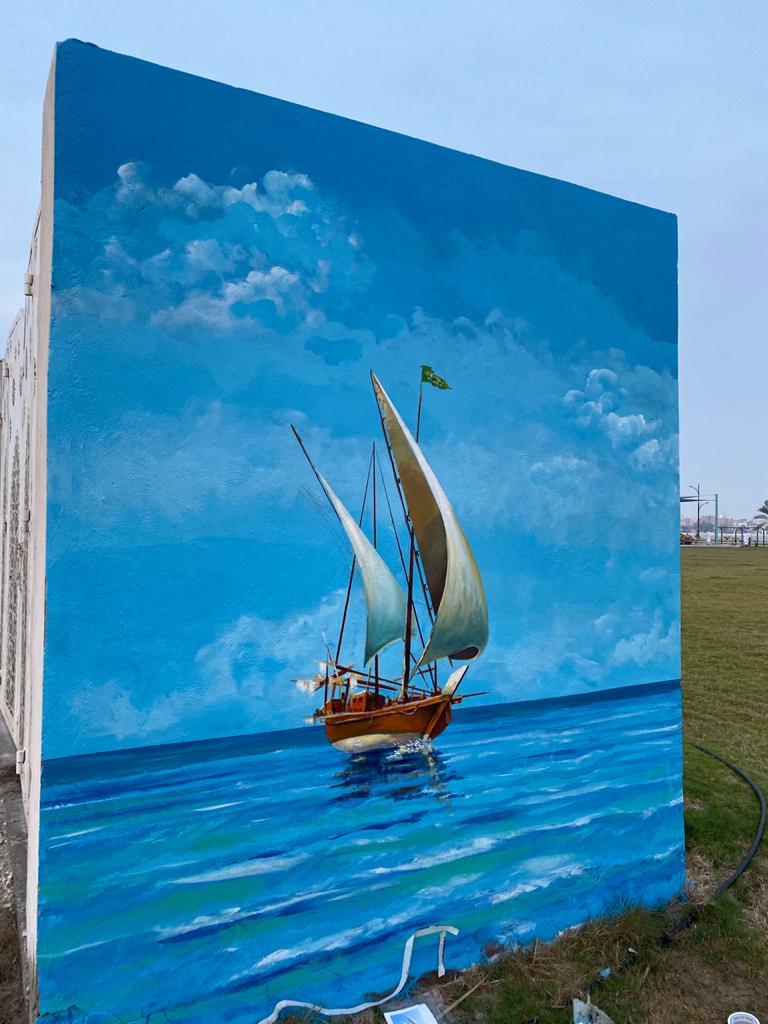 بدعم من بلدية القطيف فنان تشكيلي يرسم لوحة فنية عن الموروث الشعبي على أحد جداريات الواجهة البحرية